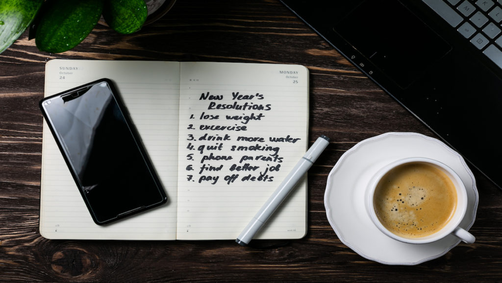 Arial view of New Years Resolution List in notebook, sitting on dark oak table with coffee, an electronic device and a pen