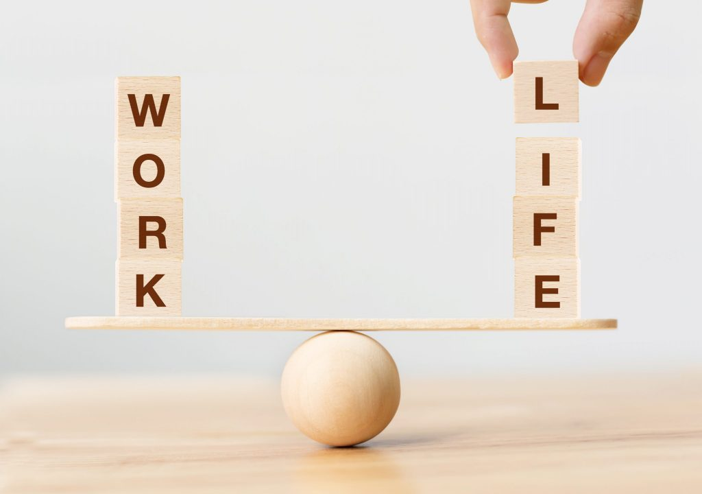 """Letter blocks making up the words """"Work"""" and """"Life"""" sit on a balancing stool as a hand places the """"L"""" to the word Life."""
